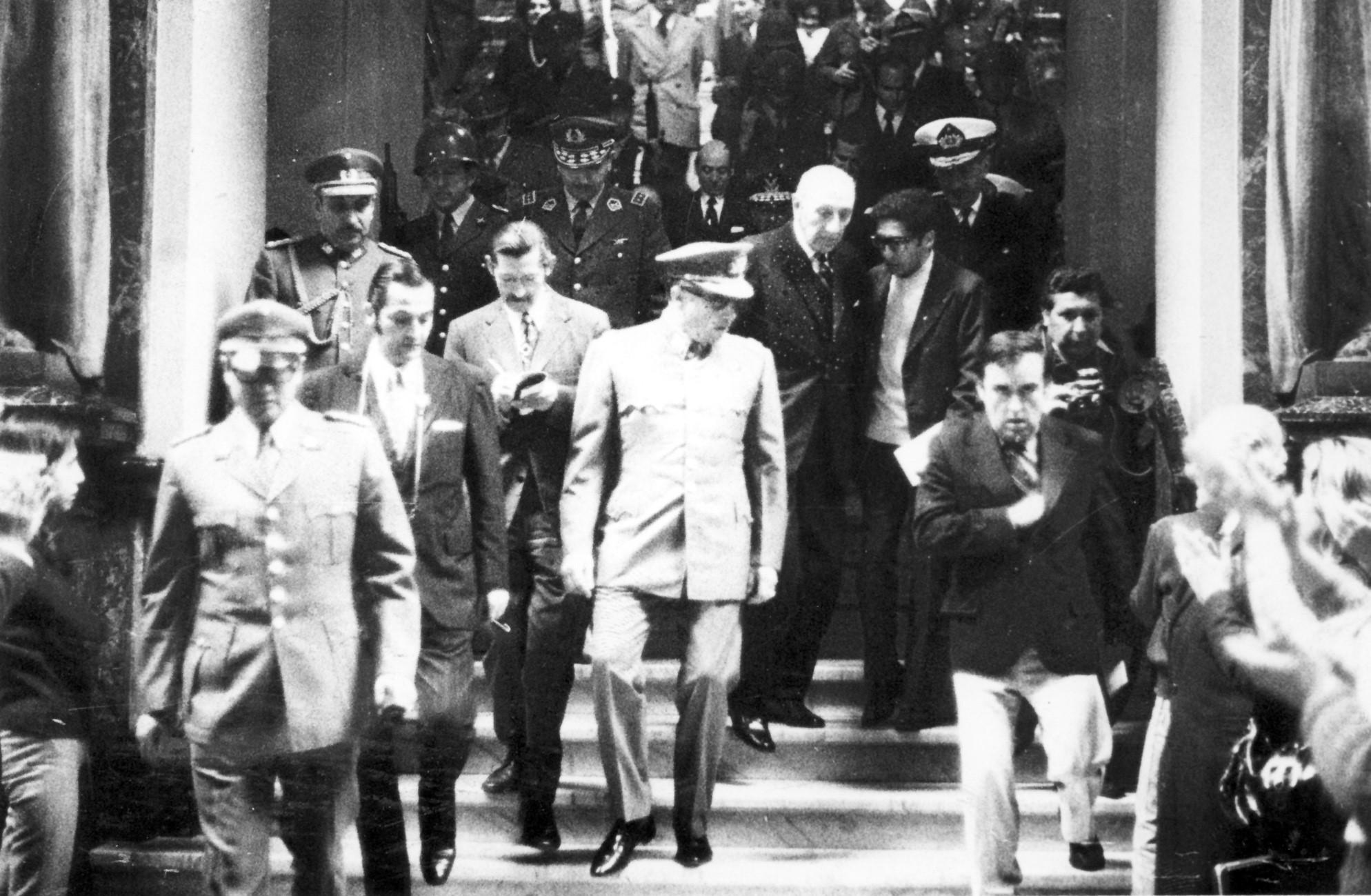 Pinochet abandona el Palacio de los Tribunales luego de una visita a la Corte Suprema. Atrás el ministro Urrutia Manzano y de lentes el periodista Otón Gutiérrez