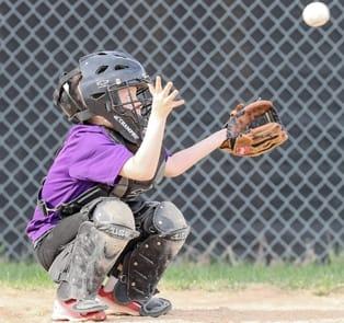 """""""Con el ojo en la bola, el cátcher de 'The Twin Metals Rockies' de la Liga Infantil de Ely"""", dice el periódico local."""