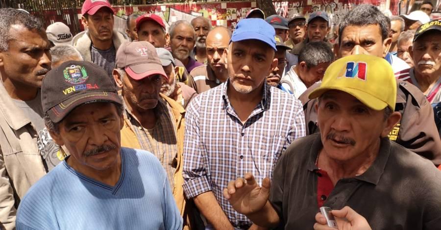 """Los dos voceros del movimiento de ex trabajadores de Exxon Mobil portando sombreros con las insignias patrias de Venezuela y con la """"M"""" usada por Nicolás Maduro en su última campaña presidencial. Foto: Andrés Almeida"""