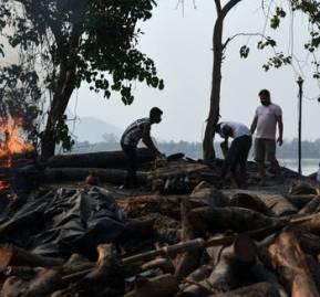 Trabajadores municipales incineran a víctimas de la covid-19 en Guwahati, India, el 25 de abril de 2021. Shutterstock / Talukdar David