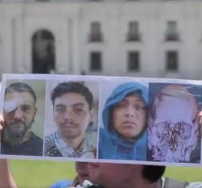 Un manifestante muestra una imagen de los heridos frente a La Moneda en la marcha de la Coordinadora de Víctimas de Traumas Oculares.